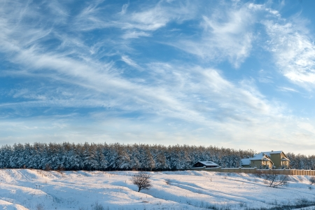 Winter landscape with the house on the edge of the wood, the trees is filled up with snow, beautiful sky photo