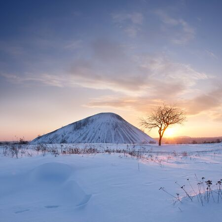 Winter landscape with waste heap in snow and majestic clouds in the sky photo