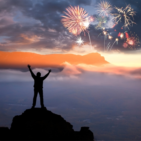 A man at mountain top with open arms, beautiful holiday fireworks in sky, feeling of freedom
