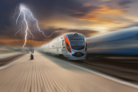 High-speed train passing station with motion blur, majestic clouds and lightning on background