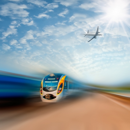 fast train: High-speed commuter train and airplane with motion blur, majestic clouds and sun