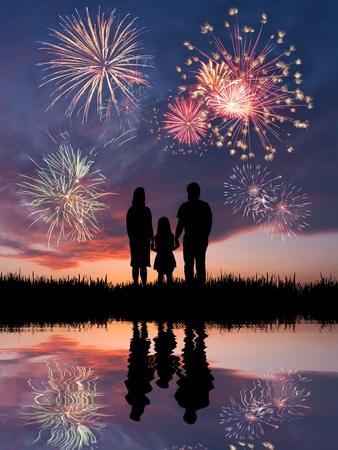 juli: De gelukkige familie ziet er prachtig kleurrijk vakantie vuurwerk in de avondlucht met majestueuze wolken