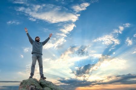 A man standing at mountain top with open arms, beautiful sunrise on background photo