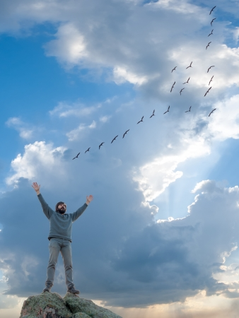 A man standing at mountain top with open arms, flight of flying birds, feeling of freedom photo