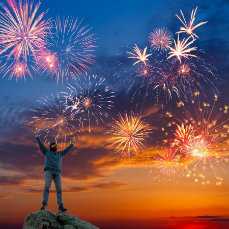 A man standing at mountain top with open arms on beautiful holiday fireworks background, feeling of freedom
