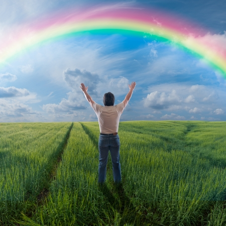 A man standing with open arms, rainbow in heavens, feeling of freedom