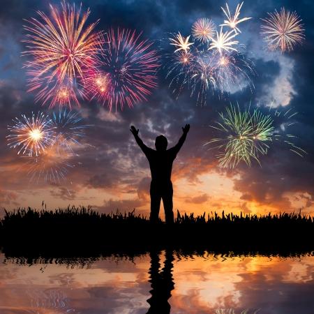 julio: Un hombre de pie con los brazos abiertos, mira los fuegos artificiales hermosas vacaciones, sensación de libertad