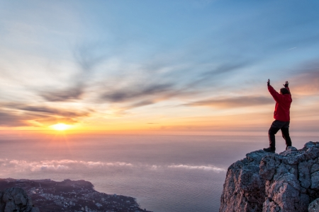 A man standing at mountain top with open arms set against a beautiful sunrise, feeling freedom Фото со стока - 18517950