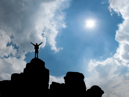 Happy man standing at mountain top with open arms, sun in blue sky on background
