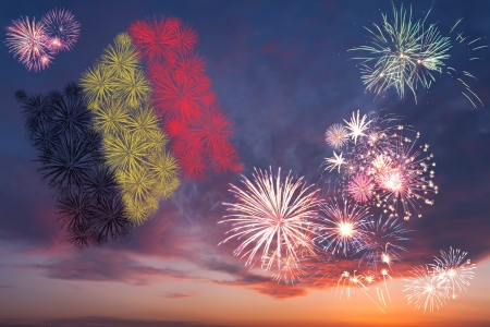 Beautiful colorful holiday fireworks with national flag of Belgium, evening sky with majestic clouds