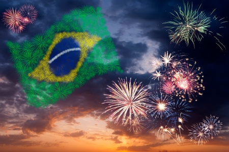 Beautiful colorful holiday fireworks with national flag of Brazil, evening sky with majestic clouds