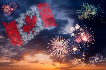 Beautiful colorful holiday fireworks with national flag of Canada, evening sky with majestic clouds Stock Photo