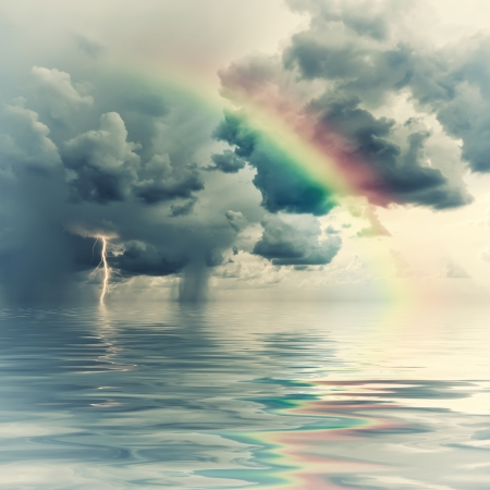 Vintage rainbow over ocean, thunderstorm with rain and lightning on background Stock Photo