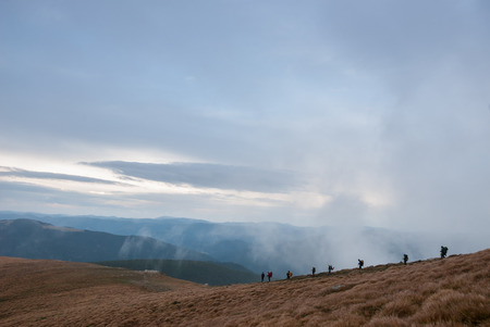 The group of brave travelers coming down from the mountain in the clouds photo