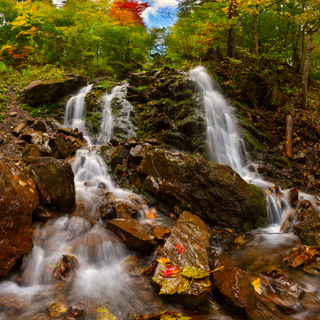 Autumn landscape with waterfall in the mountains photo
