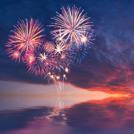 Fireworks in the sky in the form of heart reflection in water