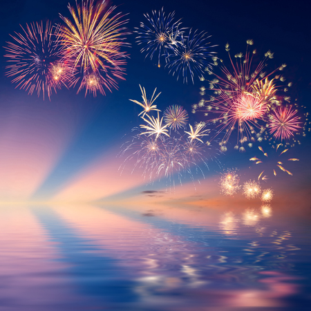 christmas in july: Colorful holiday fireworks in the evening sky reflection in water Stock Photo