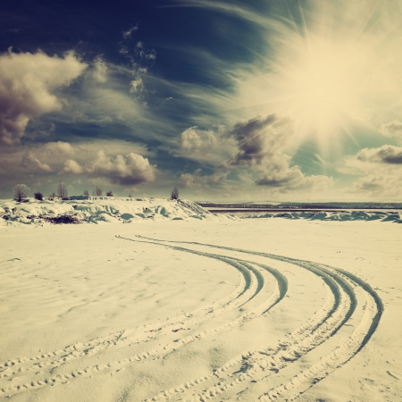 Vintage winter landscape with tire trace on snow photo