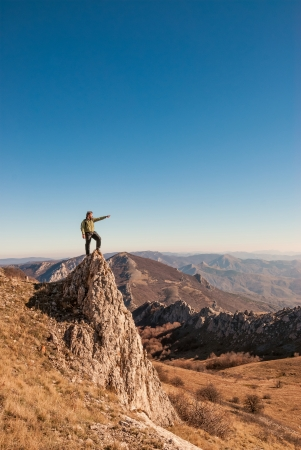 A happy traveler on a mountain top looking ahead. Active, healthy lifestyle  photo