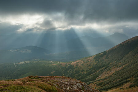 Landscape with sunbeams from clouds light the valley in the mountains photo