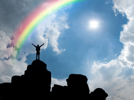 Happy man standing at mountain top, sun and rainbow in blue sky
