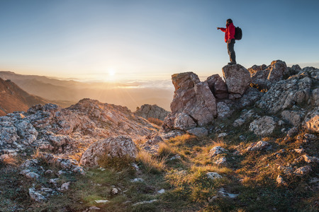 A happy traveler on a mountain top looking ahead. Shows his hand toward the horizon photo