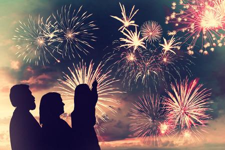 julio: La familia feliz se ve fuegos artificiales de vacaciones en el cielo de la tarde
