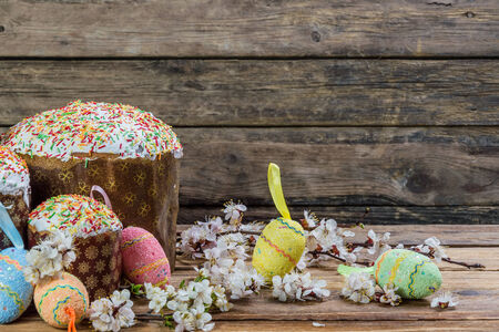 Easter eggs, flowers and cake on wooden background photo