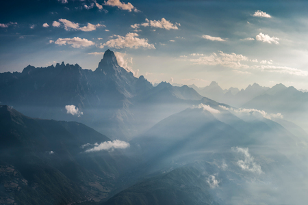 Landscape with majestic mountains in the blue haze and a beautiful sky with clouds