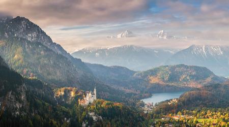Landschap met majestueuze mening over vallei met sprookjeskasteel en Alpsee, bergen op achtergrond