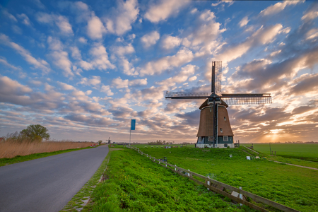 holland landscape: Traditional Holland landscape with road and windmill, majestic sky on sunrise
