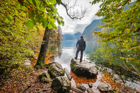 deutschland: A man stands on rock and looking at the wonderful autumn lake, seasonal landscape, Koenigsee, Bayern, Deutschland