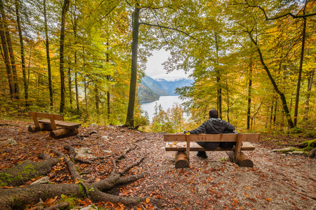 A man sits on bench and looking at the wonderful autumn lake, seasonal landscape, Koenigsee, Bayern, Deutschland