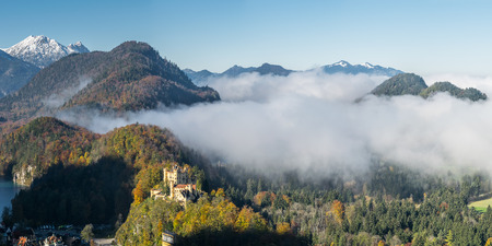 Beautiful bavarian landscape with castle, mountains and clouds