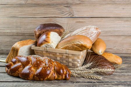 Assorted breads and wheat ears on old wooden board, food background