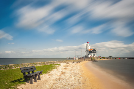 Landscape with lighthouse on bank, clouds and sun in sky, seascape, Marken, Holland Banco de Imagens
