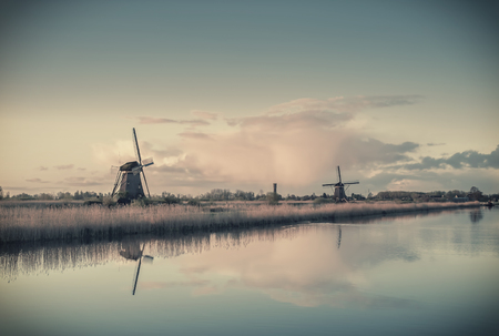 Vintage landscape with windmills and majestic sky reflection in water, retro film filter