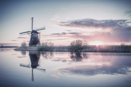 vintage landscape: Vintage landscape with windmills and majestic sky reflection in water, retro film filter