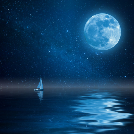 Lonely yacht in calm ocean, full moon and stars reflection in water. Landscape with milky way Фото со стока