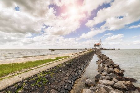 marken: Landscape with lighthouse on bank, clouds and sun in sky, seascape