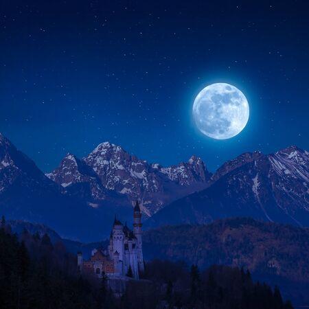 Neuschwanstein castle in moon light, landscape with stars over mountain, Bavaria