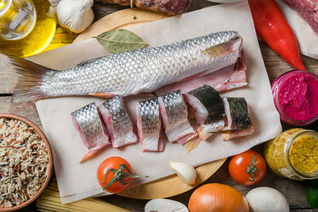 gherkins: Split raw fish and vegetables on wooden tables. Ready for cooking, food background