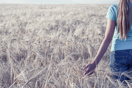 Teenager in field looks at wheat, vintage picture