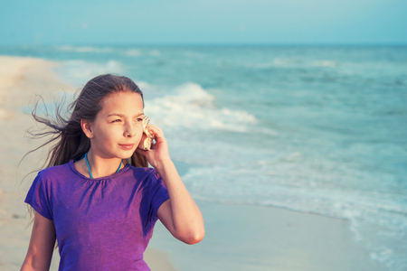 Beautiful teenage girl with seashell listening sound of waves on beach, summer vacation, vintage style