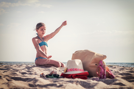Cute white girl teenager resting on beach, summer background, selective focus, vintage style