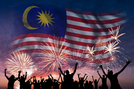 Happy people are looking holiday fireworks with flag of Malaysia in sky, independence day 스톡 콘텐츠