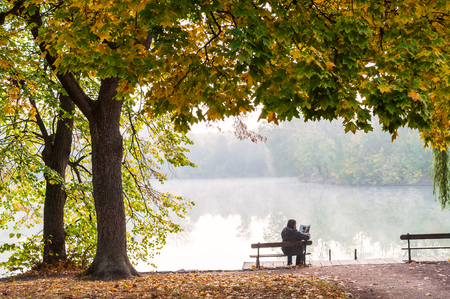 Autumn landscape with foggy lake in park. Man on bench read magazine. Beautiful seasonal view