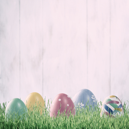 Painted eggs on retro easter holiday background, spring grass and wild flowers, copy space. Vintage stylization, film filter