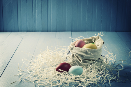 Easter holiday background with painted eggs on wooden boards, copy space. Vintage stylization, retro film filter
