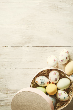 Easter holiday background with eggs painted and floral decorations on wooden boards, copy space. Vintag stylization, retro film filter